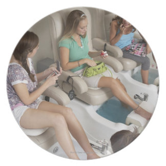 Three young women receiving pedicure in beauty dinner plates