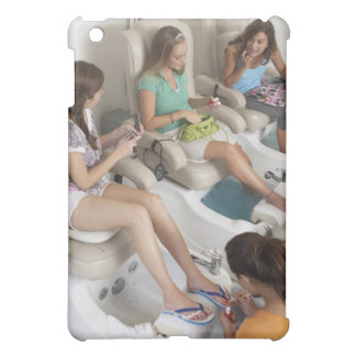 Three young women receiving pedicure in beauty iPad mini cases