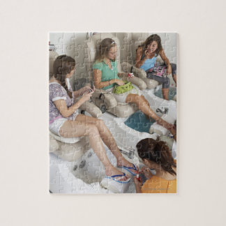 Three young women receiving pedicure in beauty jigsaw puzzle