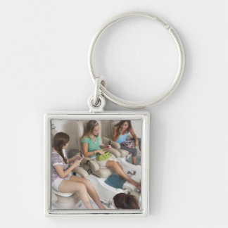 Three young women receiving pedicure in beauty Silver-Colored square key ring