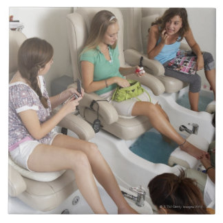 Three young women receiving pedicure in beauty tile