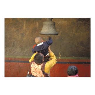 Tibetan Buddhist monk lifting a boy to ring a Photographic Print