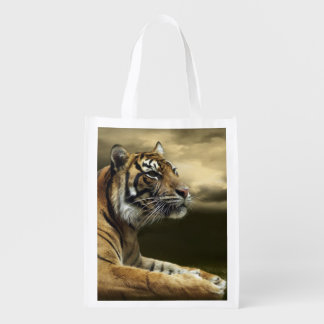 Tiger looking and sitting under dramatic sky reusable grocery bag