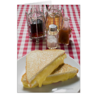 Toasted cheese sandwiches on plate, vinegar, card