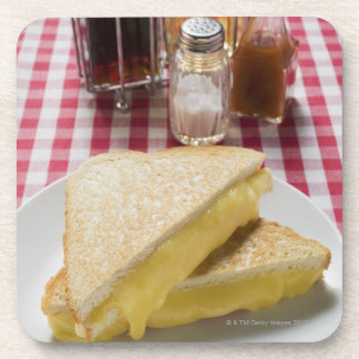 Toasted cheese sandwiches on plate, vinegar, coaster
