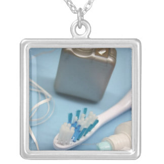 Toothbrush, toothpaste and floss. silver plated necklace