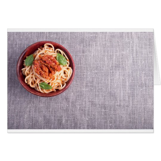 Top view of a grey mat with a spaghetti card