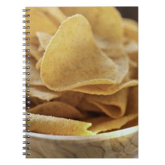 Tortilla chips in wooden bowl spiral notebook