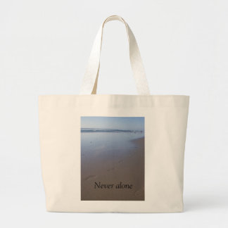 Tote features shore with footprints in the sand.