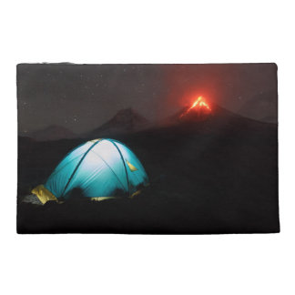 Tourist tent on background of erupting volcanoes travel accessories bags