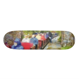 Toy train and adult passengers skate board deck