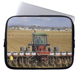 Tractor pulling a seed corn planter. laptop sleeve