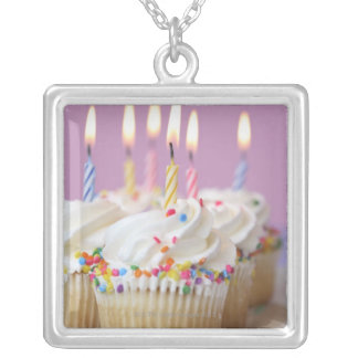 Tray of birthday cupcakes with candles silver plated necklace