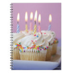 Tray of birthday cupcakes with candles spiral notebooks