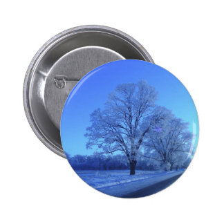 Tree covered in snow on barren landscape. 6 cm round badge