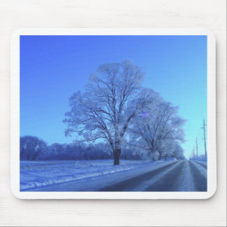 Tree covered in snow on barren landscape. mousepad