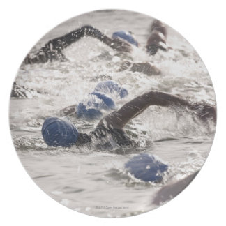 Triathletes competing in swim leg of triathlon. dinner plates
