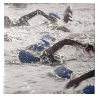 Triathletes competing in swim leg of triathlon. large square tile