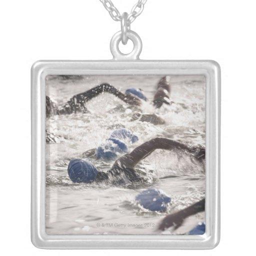Triathletes competing in swim leg of triathlon. necklace