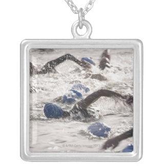 Triathletes competing in swim leg of triathlon. square pendant necklace