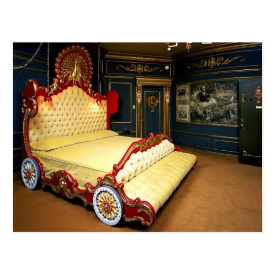 Tufted sleigh bed with wheels and a peacock
