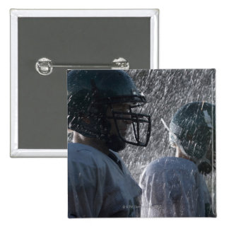 Two American football players in rain, side view Pin