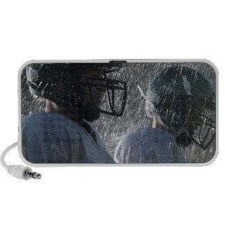 Two American football players in rain, side view Speaker