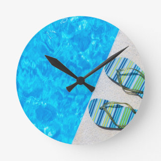Two bathing slippers on edge of swimming pool clock
