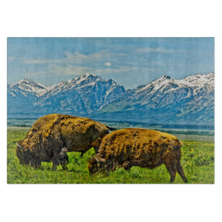 Two bison grazing cutting board