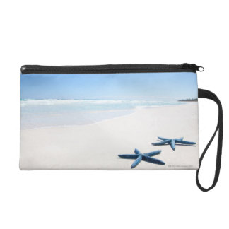 Two blue starfish at water's edge on tropical 2 wristlet purse