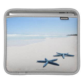 Two blue starfish at water's edge on tropical 2 iPad sleeve