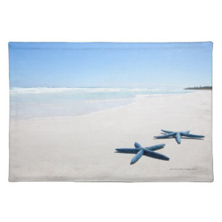 Two blue starfish at water's edge on tropical 2 placemat