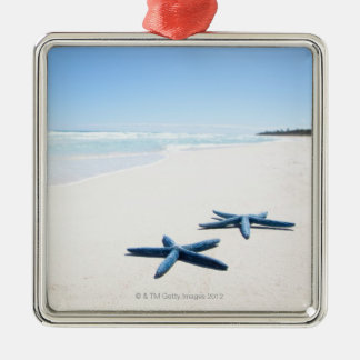 Two blue starfish at water's edge on tropical 2 Silver-Colored square decoration