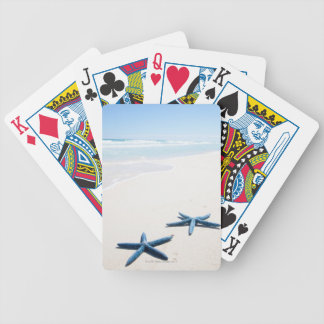 Two blue starfish at water's edge on tropical bicycle playing cards