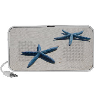 Two blue starfish at water's edge on tropical iPod speaker