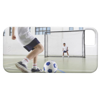 Two boys, aged 8-9, playing soccer in a school case for the iPhone 5