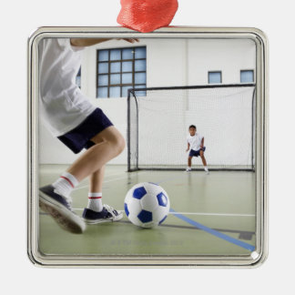 Two boys, aged 8-9, playing soccer in a school christmas ornament