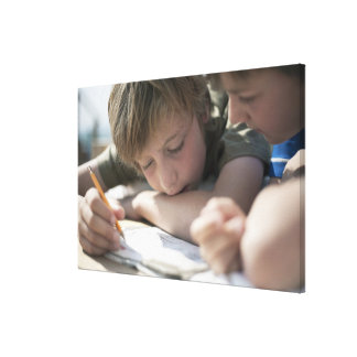 Two boys writing together canvas print