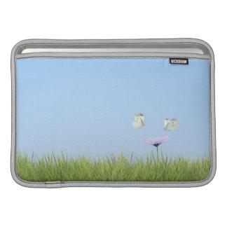 Two butterflies hovering over flower MacBook air sleeve