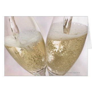 Two champagne flutes being filled with sparkling card