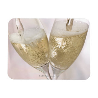 Two champagne flutes being filled with sparkling rectangle magnets