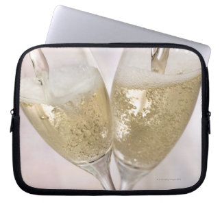 Two champagne flutes being filled with sparkling laptop sleeve