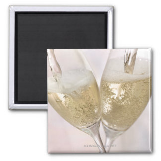 Two champagne flutes being filled with sparkling refrigerator magnets