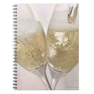 Two champagne flutes being filled with sparkling spiral notebook