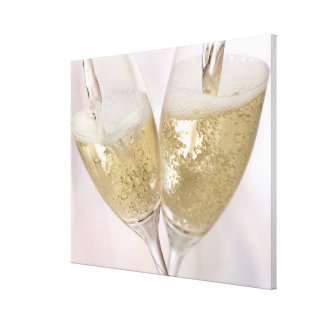 Two champagne flutes being filled with sparkling stretched canvas prints
