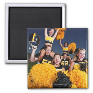 Two cheerleaders riding on shoulders of football magnet