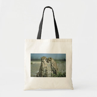 Two cheetahs sitting face to face tote bag