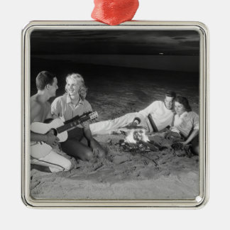 Two couples on beach sitting around campfire christmas ornament