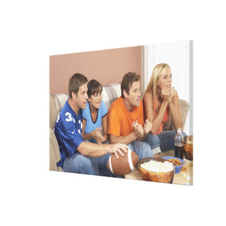 Two couples watching football in living room stretched canvas print