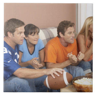 Two couples watching football in living room tile